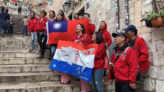 海歸人聲合唱團榮獲雙金殊榮,團員舉起國旗同慶。