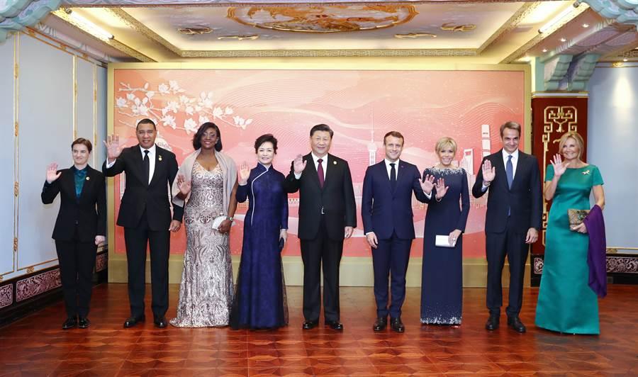 大陸國家主席習近平夫婦4日晚間宴請出席中國國際進口博覽會的各國貴賓,包括法國總統馬克龍夫婦(右4,3)、牙買加總理霍爾尼斯夫婦解(左2,3)、希臘總理米佐塔基斯夫婦(右2,1)、塞爾維亞總理布爾納比奇(左1)等人。(圖/新華社)