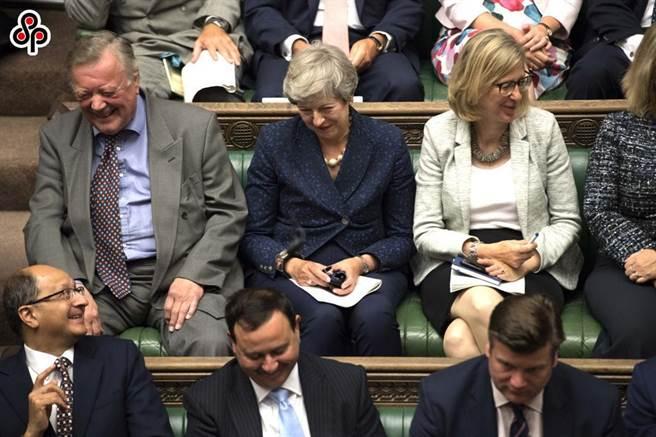 英國國會解散並提前舉行大選前,無官一身輕的英國前首相梅伊(後排中)出席會議。。(新華社)