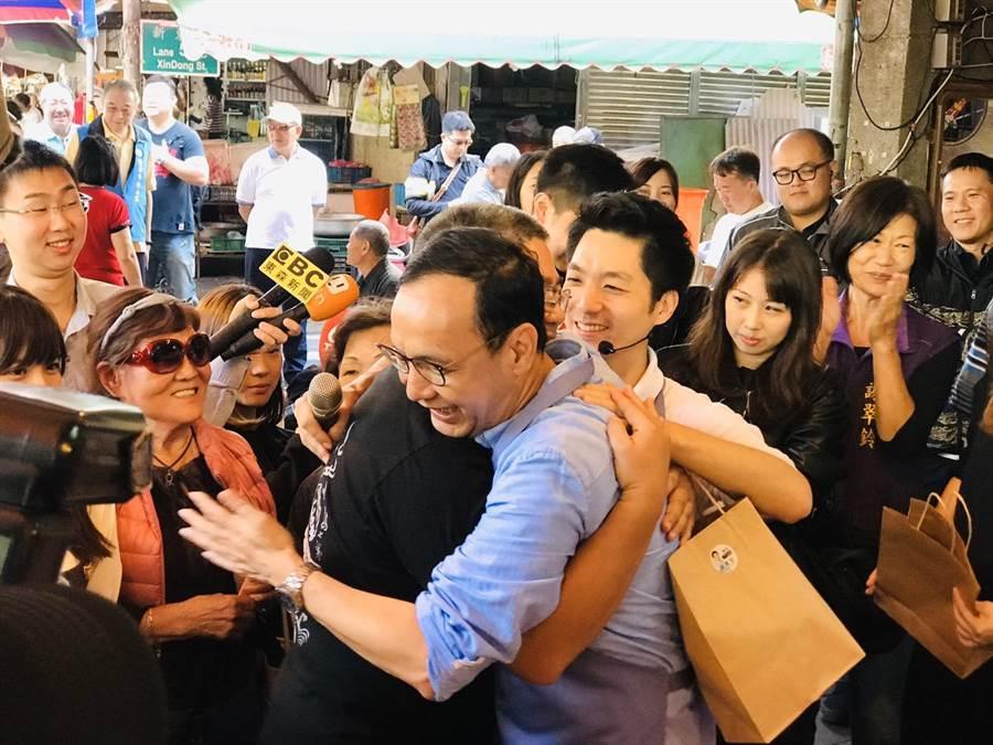 前新北市長朱立倫(中)7日陪立委蔣萬安(右)掃街做公益,和民眾熱情擁抱。(張穎齊攝)