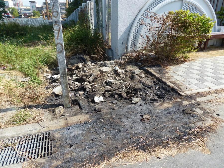 起火點位在家扶心館門口右前方界址樁處,現場雜草和廢棄物燒成一片焦黑還有濃濃塑膠味,家扶圍牆也被燻黑一小塊。(謝瓊雲攝)
