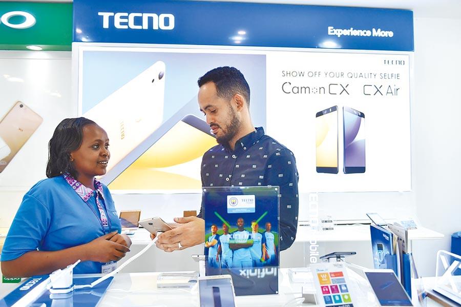傳音手機成功打進非洲市場,圖為2017年5月9日,在肯亞首都內羅畢市中心一家手機店,銷售人員向顧客介紹深圳手機廠商生產的傳音手機。 (新華社)