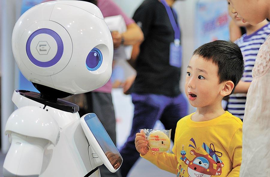 一名小朋友在瀋陽國際機器人大會上,與機器人互動。(中新社資料照片)