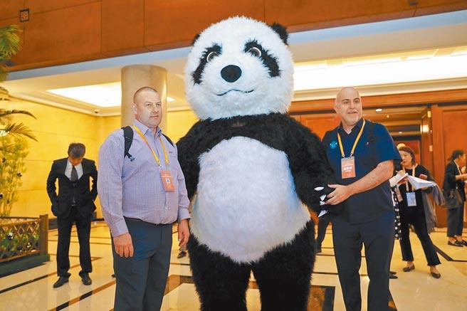 參加進博會嘉賓與大熊貓人偶合影。