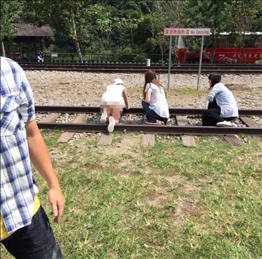 白衣短裙妹露出雪臀跪趴在鐵軌上拍照,引起網友不滿。(圖/翻攝自加藤軍路邊隨手拍)
