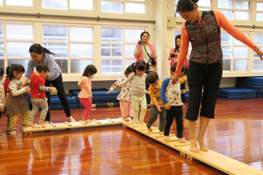 107學年度於光復國小附幼辦理《0-5歲幼兒運動遊戲百科》教學觀摩活動,幼生們由老師帶領,正使用可移動式遊具在闖關活動中保持平衡前進。