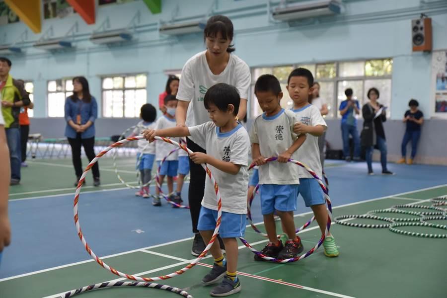 107學年度於崇德國小附幼辦理《0-5歲幼兒運動遊戲百科》教學觀摩活動,幼生們使用呼拉圈練習,教師在旁協助指導。