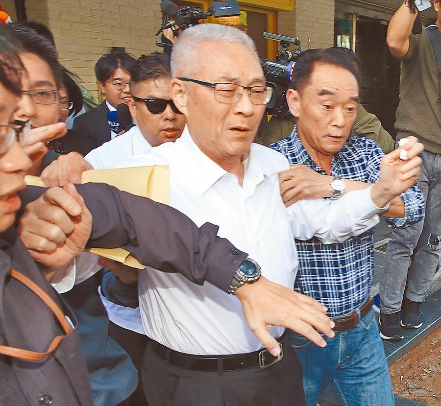 國民黨主席吳敦義7日與黨籍立委餐敘後,不願回應記者追問不分區提名問題,在隨扈保護下離去。(陳君瑋攝)