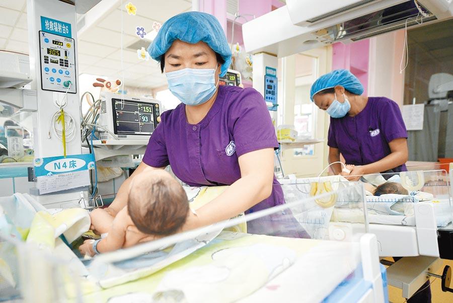 2018年5月10日,寧夏銀川市婦幼保健院工作人員護理新生兒。(新華社)