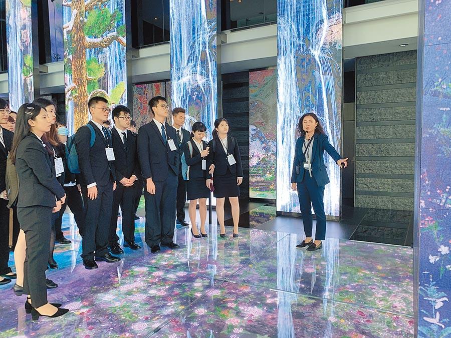 中信金融管理學院首屆校友張妮宸(右一)向新生介紹中國信託大廳數位互動藝術裝置。(中國信託提供)