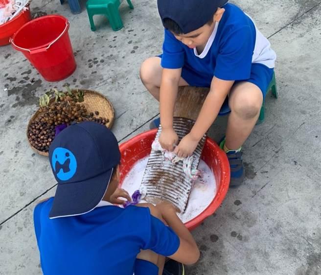 南安國小學童到古寶無患子生技公司進行戶外教學,體驗用無患子殼在洗衣板上搓泡泡洗衣服。(古寶無患子提供/劉秀芬台南傳真)