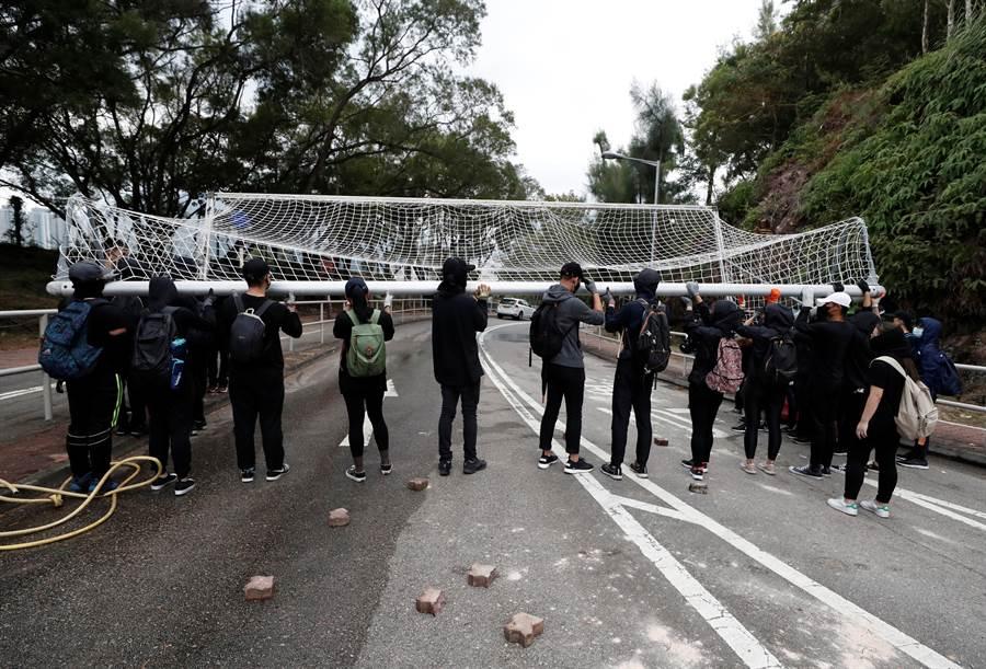 香港9所大學今日停課且停止活動,學生持續參與示威,並在校園內堵路。圖為中文大學學生以體育設施堵住校園內通道。(圖/路透)