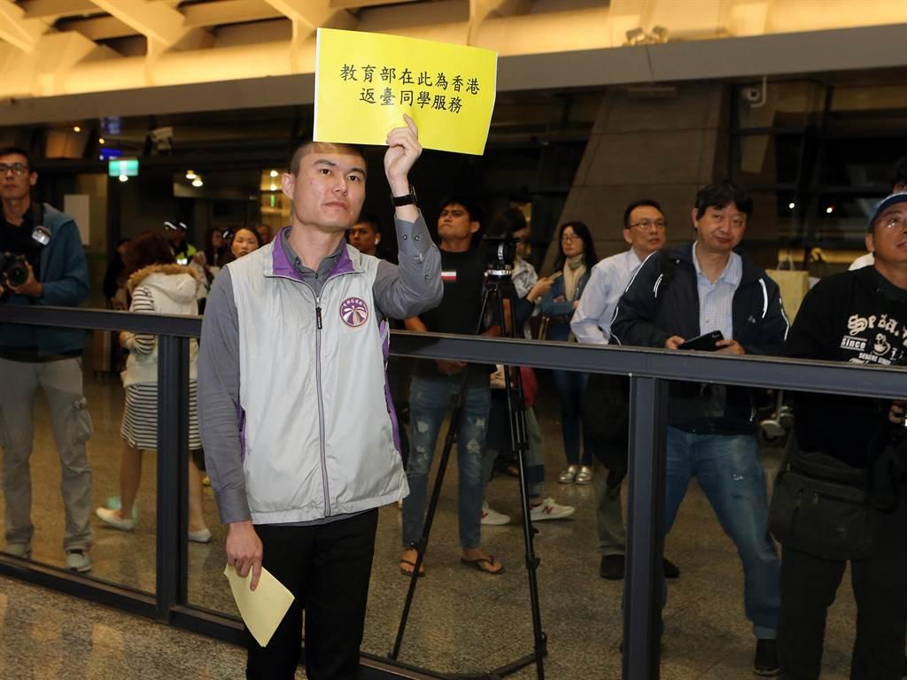 教育部官員則拿著標語在桃機第1航廈入境大廳管制區外等候,但並沒有下機學生們上前求助。(陳麒全攝)