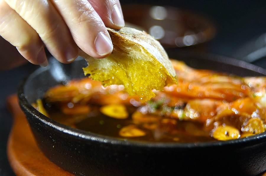 〈蒜香蝦油鮮蝦〉的蒜油極香、極誘人,知味老饕會以麵包沾食,享受美味。(圖/姚舜)