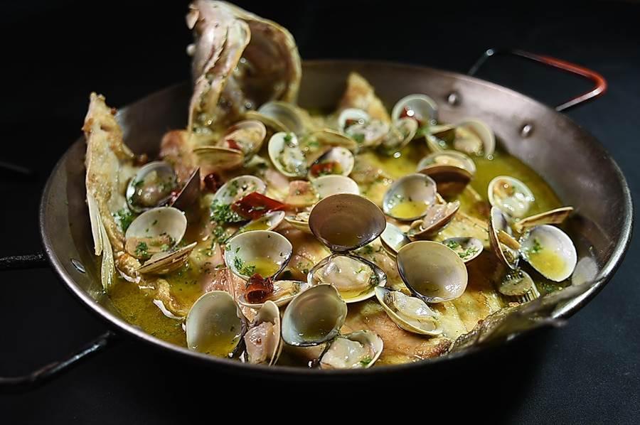 〈巴斯克烤魚〉的魚先用明火炭烤再爐烤,再舖上蒜炒蛤蜊,最後淋上糖醋醬汁,上桌時可空氣中飄散著酸香,嘗起來卻不油不膩。(圖/姚舜)