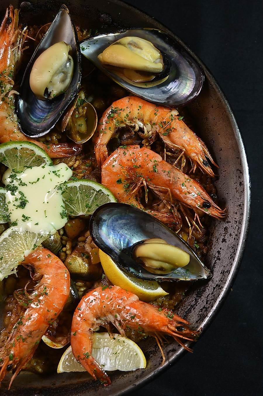 台北〈alma〉的〈西班牙海鮮飯〉每鍋1250元,可供4人享用,餡料有鮮蝦、淡菜和蛤蜊,留著米心口感的米飯中摻了魷魚丁,並用蝦油和蒜味美乃滋提味增香。(圖/姚舜)