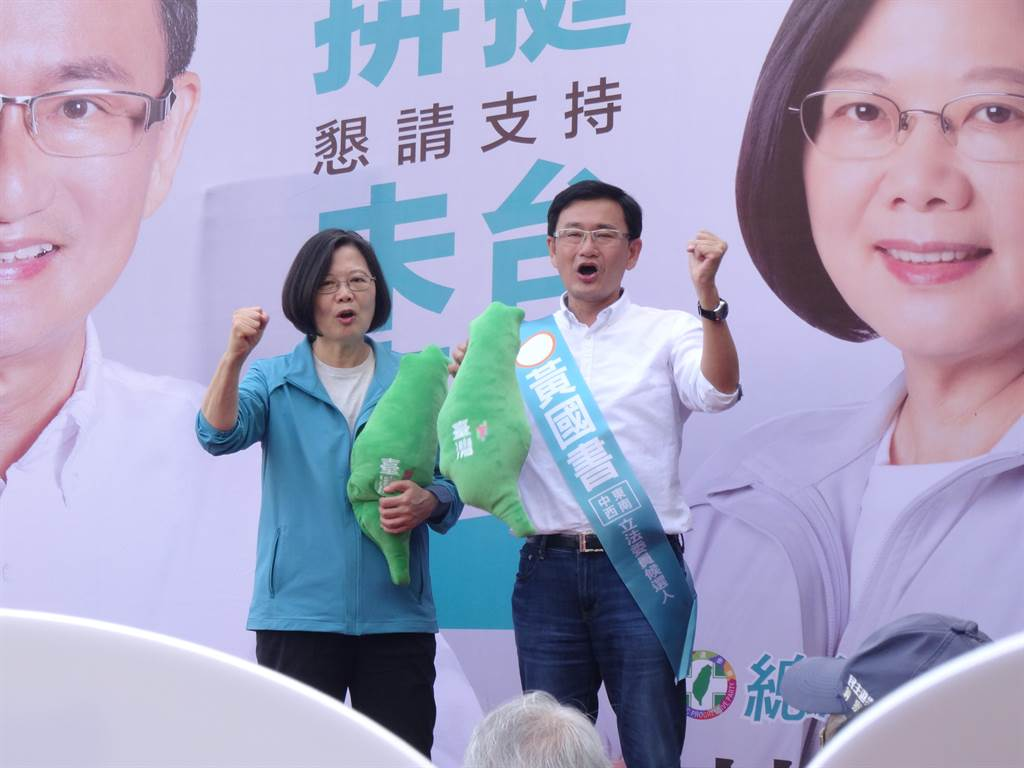 總統蔡英文致詞完,她也拿出總統府文創商品綠色的寶島抱枕致贈給黃國書。(馮惠宜攝)