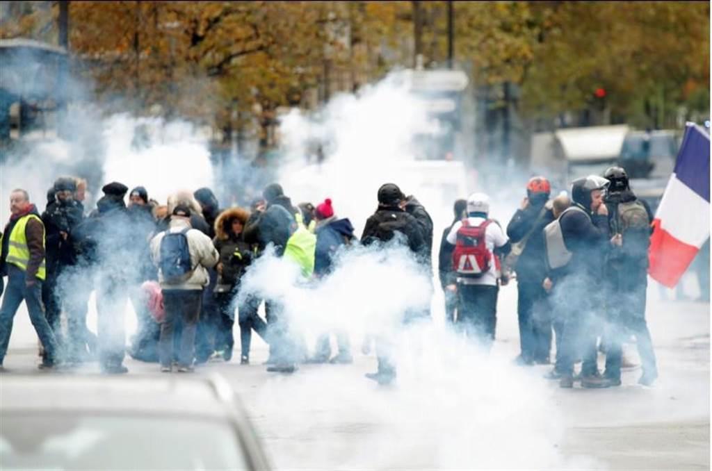 「黃背心」示威一周年,法國巴黎16日再有示威活動,群眾遭鎮壓警察施放催淚瓦斯。(路透)