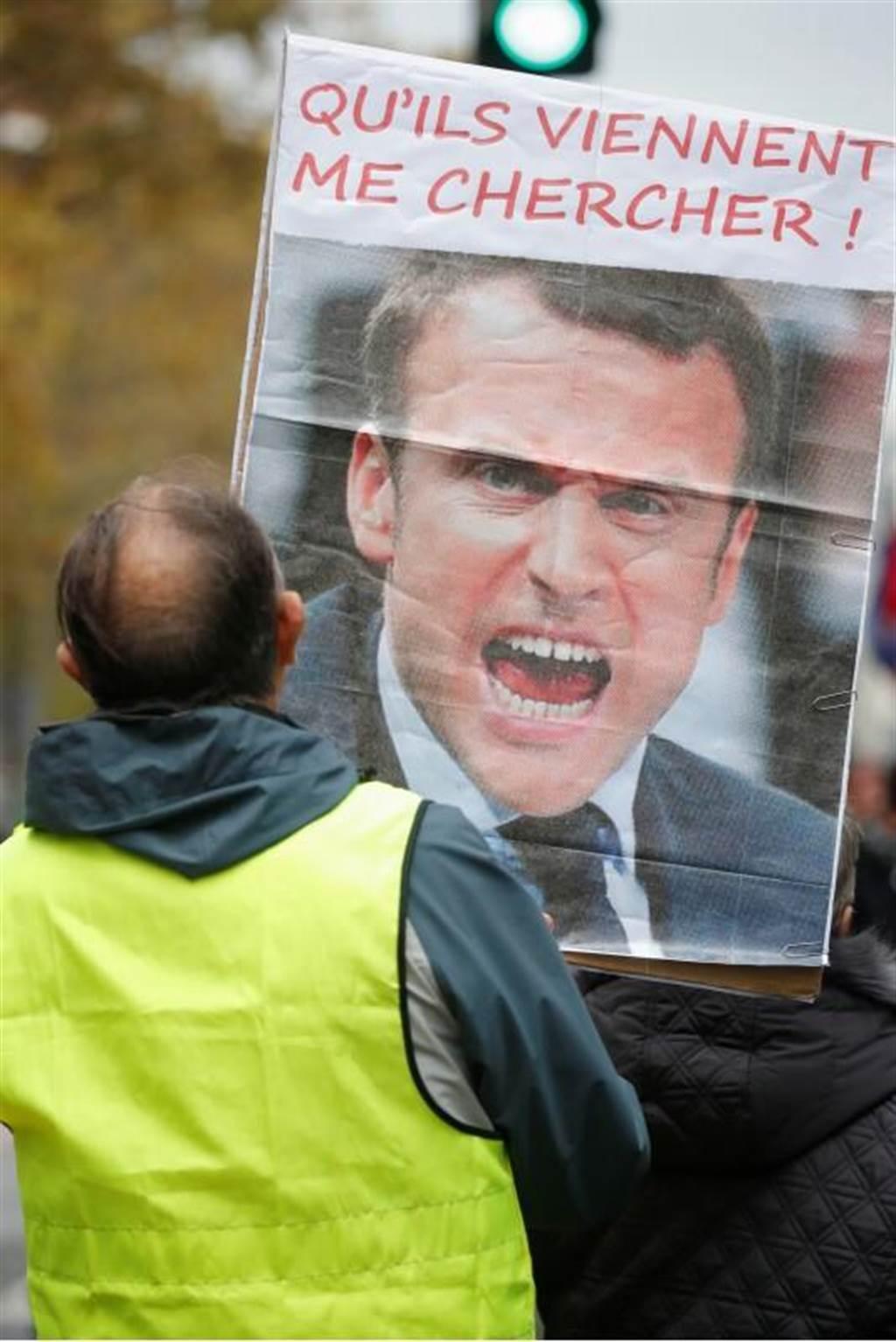 一名「黃背心」示威者16日在巴黎的活動上,舉著印有馬克洪總統人像的標語牌。(路透)