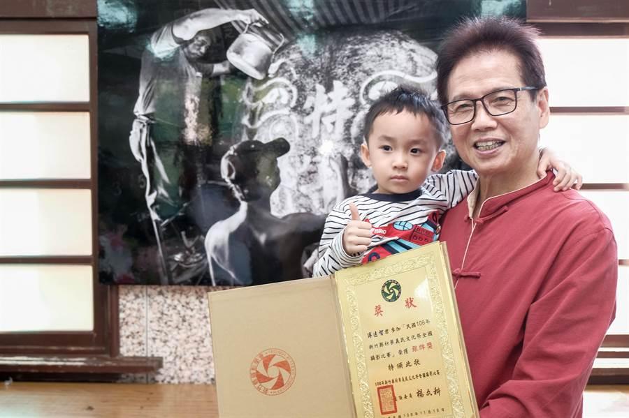 義民文化祭全國攝影比賽銀牌傅遠智與孫子合影,後為作品「特等神豬」。(羅浚濱攝)