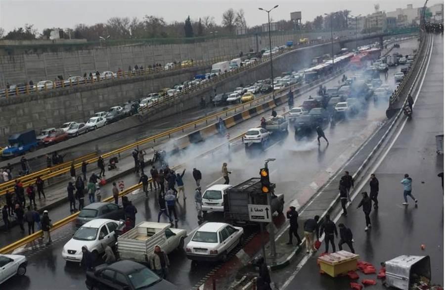 伊朗民眾16日在德黑蘭一條公路上示威,抗議汽油價格飆升。(路透)