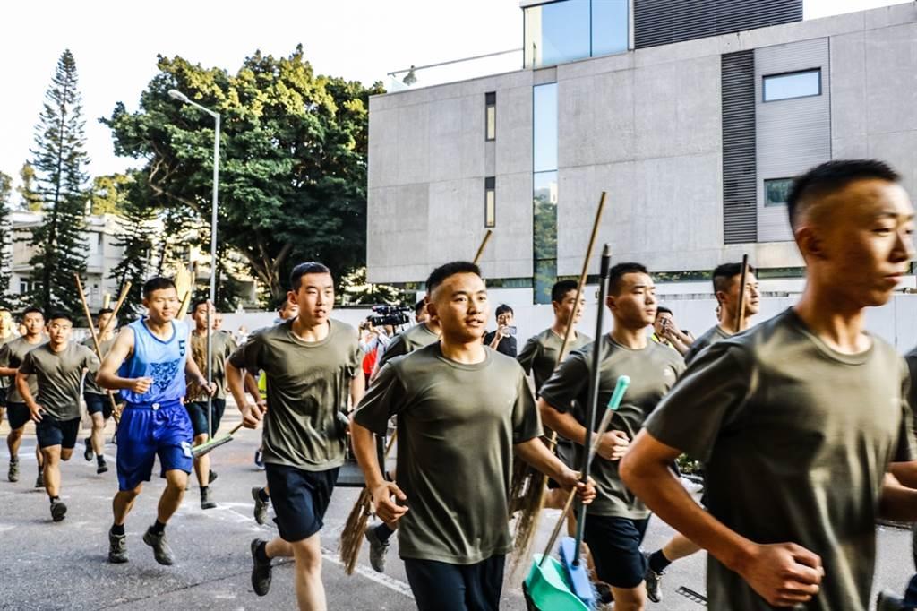 數十名解放軍駐港部隊軍人16日突現身軍營附近道路清理反送中示威人士設下的路障,引發各界關注。(圖/中新社)