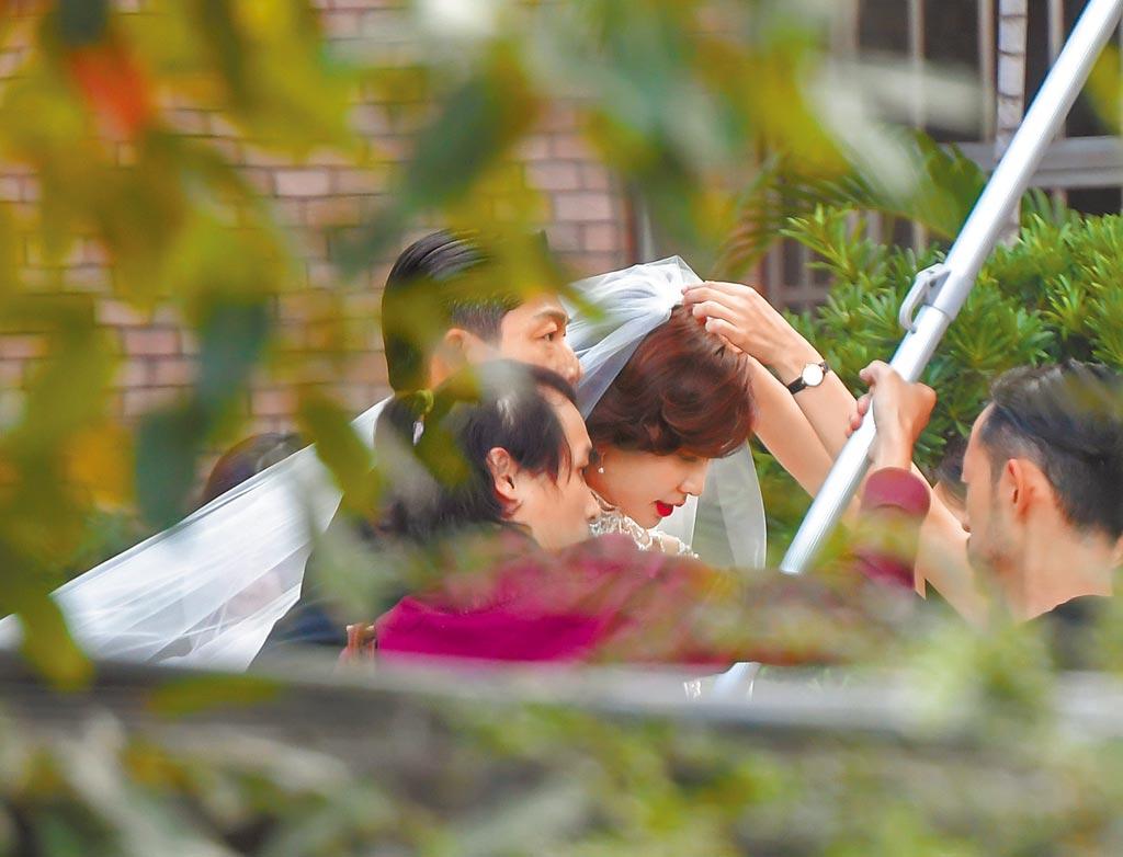 林志玲(後)與AKIRA並肩,工作人員幫忙林志玲調整白色頭紗。(盧禕祺攝)