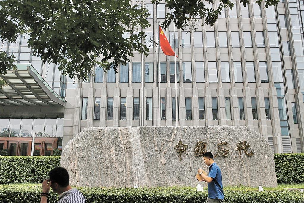 大陸中國石化位居世界500強前列,圖為行人走過北京中國石化總部。(中新社資料照片)