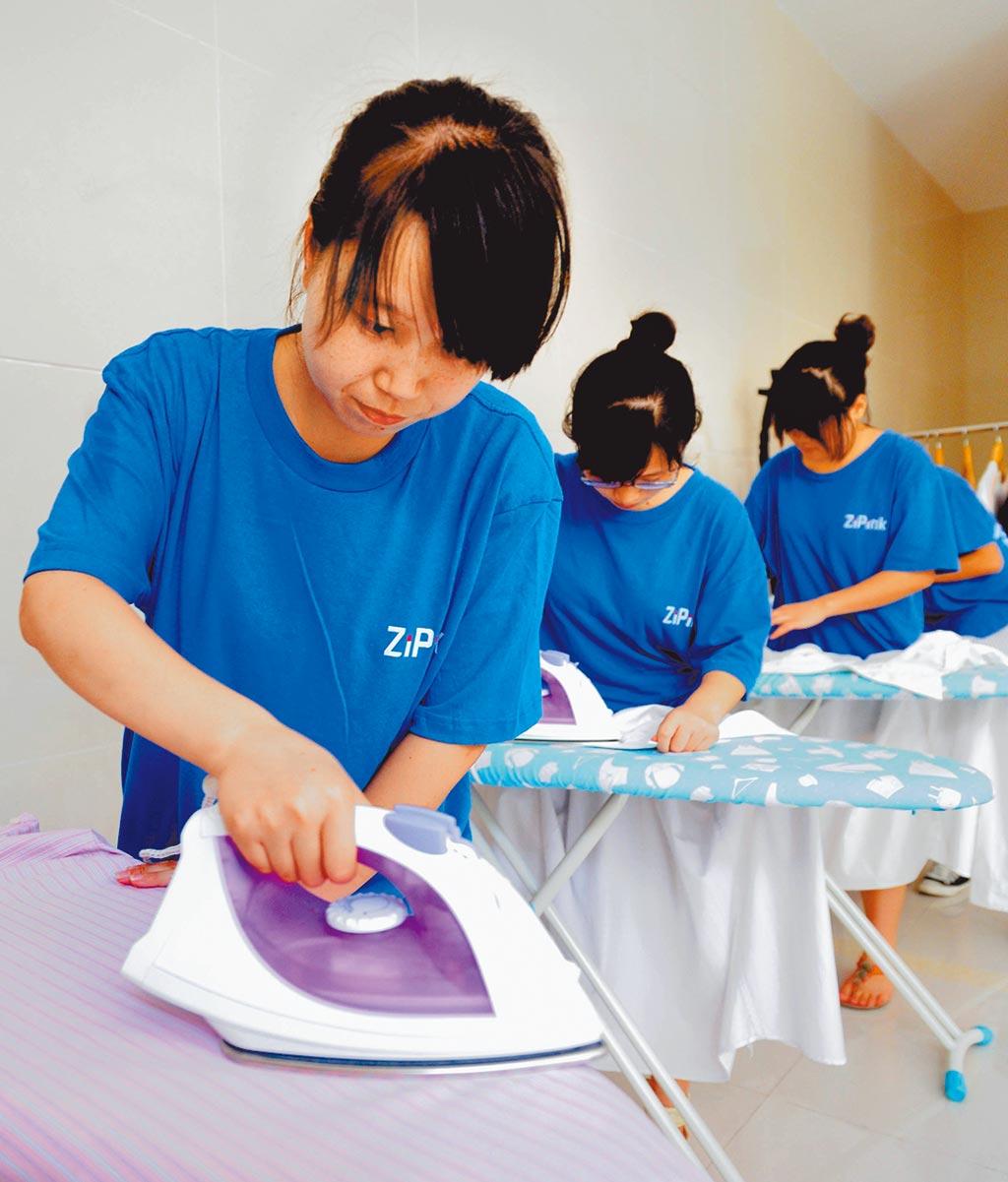 重慶大學生在基地學習熨燙衣物的專業技能。(新華社)