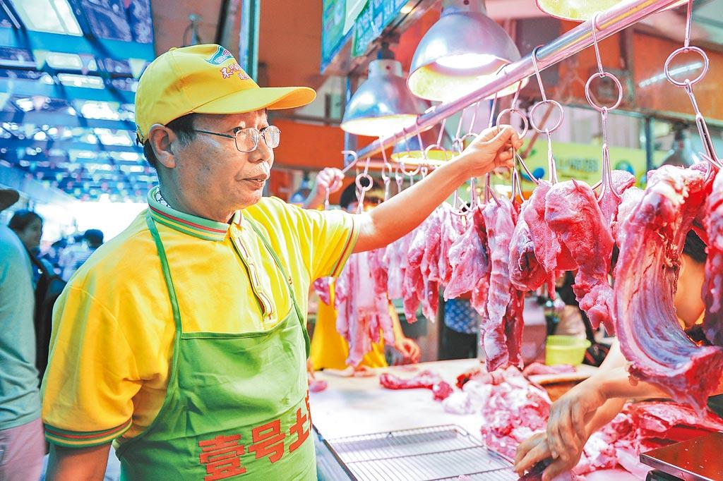 陸步軒在廣州一市場內為市民挑選豬肉。(中新社資料照片)