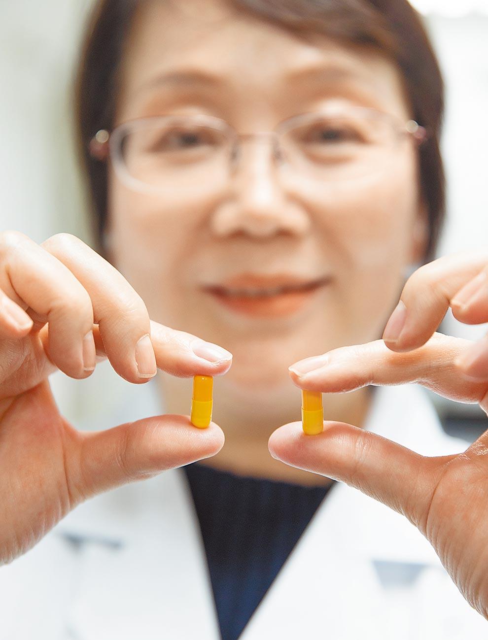 新藥發明人展示新藥樣品模型。(新華社)