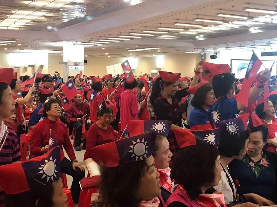 三重小巨蛋內外早已擠滿身穿國旗衣、戴國旗帽的支持者,韓國瑜競選總部副總幹事周錫瑋上台致詞後,大夥開始輪番歌唱「月亮代表我的心」、「國家」、「木棉道」等歌曲為韓國瑜的到來暖場,現場旗海飄揚、氣氛溫馨。(戴上容攝)