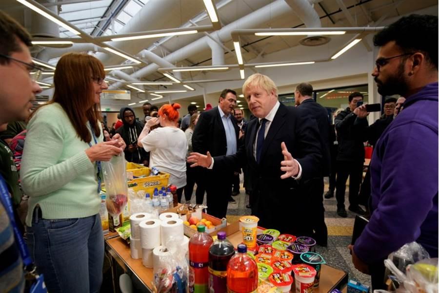 英國首相強森為了下月選戰風塵僕僕造勢,他16日前往波頓大學參訪,與教職員話家常。(路透)