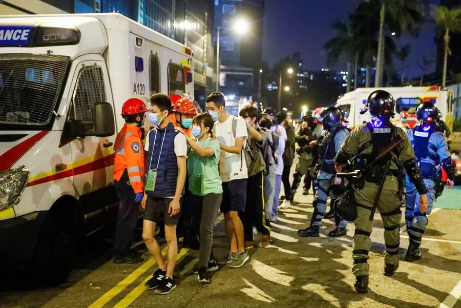 入夜以后,香港理工大学示威者已渐疲乏,陆续有受伤者与放弃抵抗者向警方投降,他们依警方指示,双手搭前者肩头鱼贯而行,进入警方安排的汽车离开。(图/路透)