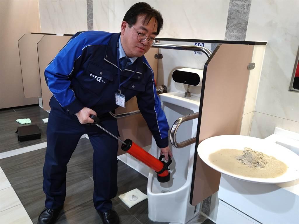 山戶伸孝以內視鏡設備,查看未清除前的男廁小便斗,裡頭有明顯的尿垢,以貫通器抽出尿垢後,臭味就明顯改善。(林雅惠攝)