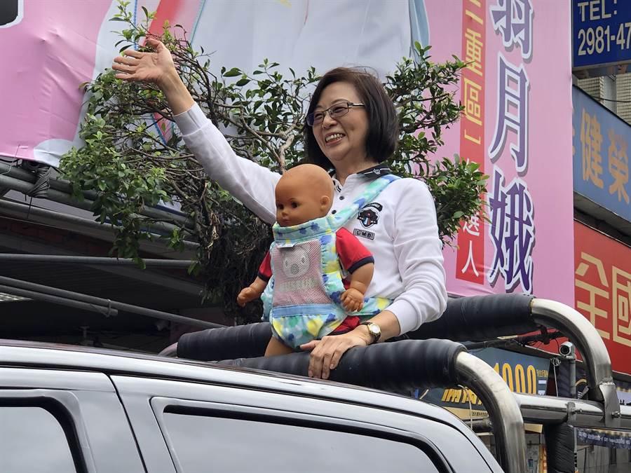 李翁月娥20日早上9時許揹著娃娃,在三重重陽路競選總部前召開登記記者會,她提出「鼓勵生育救台灣」(戴上容攝)