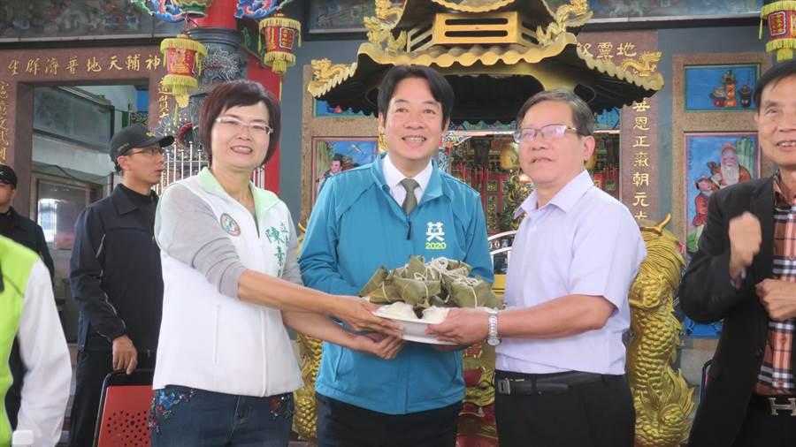 廟方代表送上包子、粽子祝福陳素月(左)、賴清德(中)兩人都能順利當選。(謝瓊雲攝)