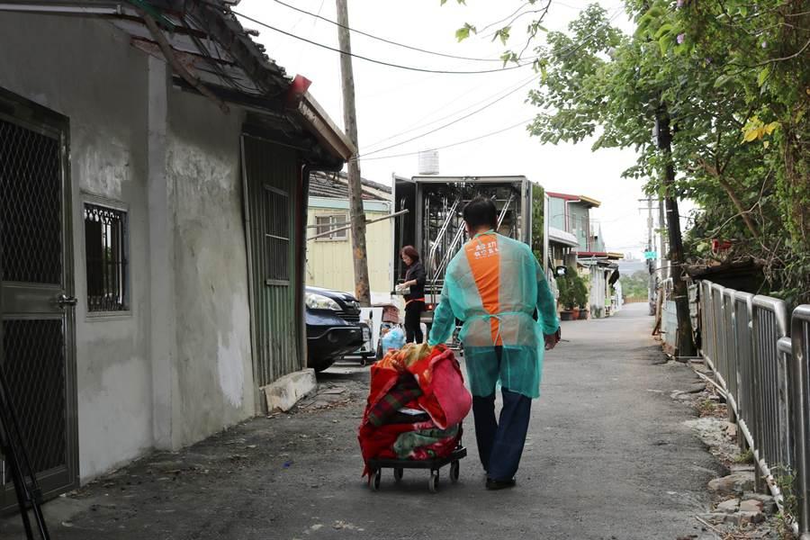 由於獨居劉阿公住處向弄狹窄,志工將床褥、枕頭等辦到巷口的乾燥車處理。(弘道老人福利基金會提供/王文吉台中傳真)