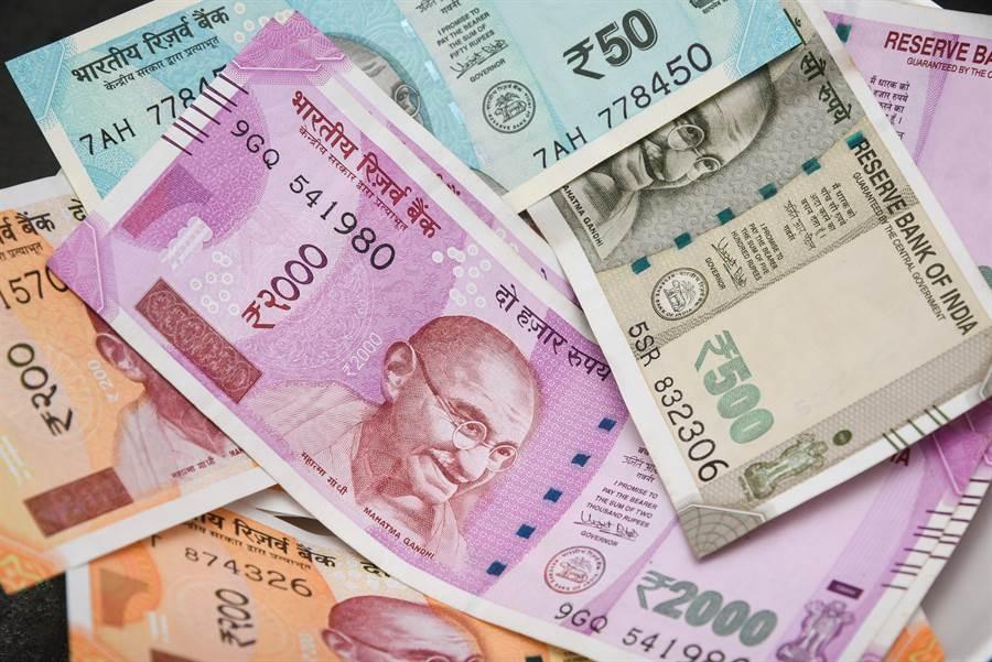 印度加爾各答大樓昨天有人從空中大撒幣,大多是面額2千、5百和1百盧比的鈔票。(摘自shutterstock)