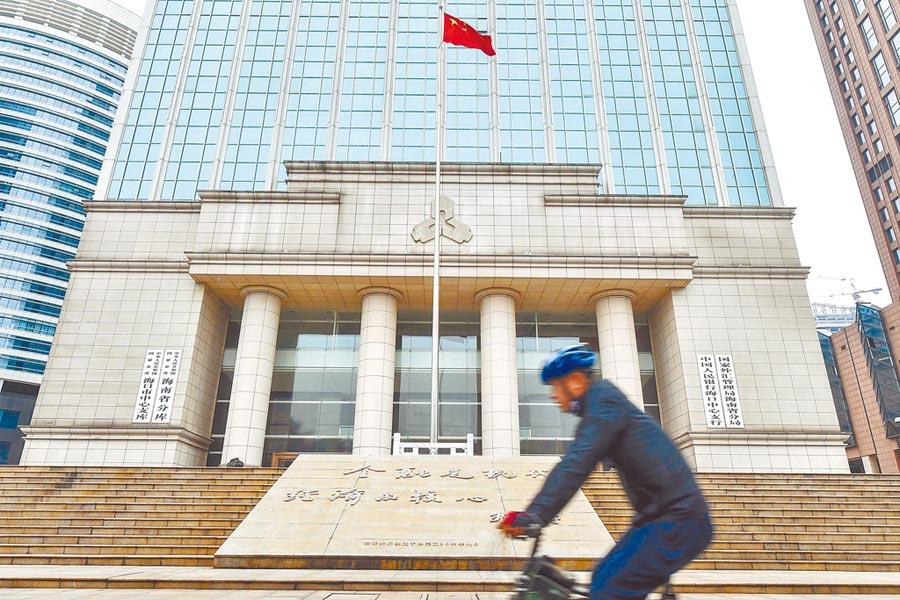 大陸央行定調貨幣寬鬆政策。圖為民眾經過中國人民銀行海口中心支行。(中新社資料照片)