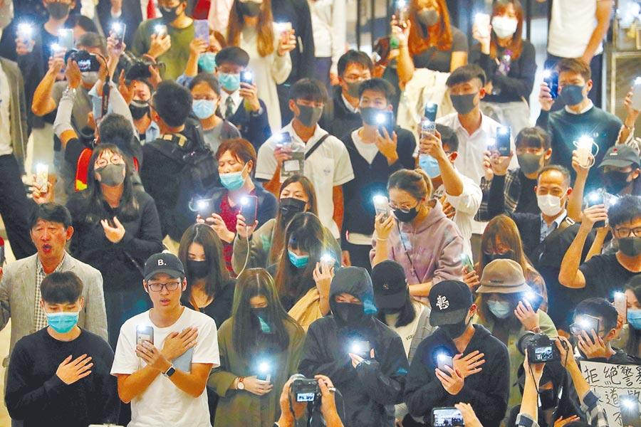 數十名蒙面示威者昨晚在香港元朗聚集,聲援抗議活動,香港防暴警到場。(美聯社)