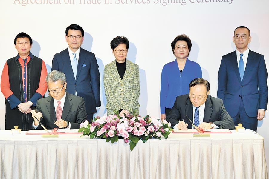 11月21日,香港財政司長陳茂波(前排左)與大陸商務部副部長王炳南(前排右)簽署《CEPA修訂協議》。後排中為香港特首林鄭月娥。(中新社)