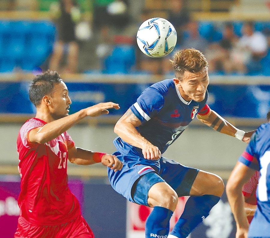 2022卡達世界盃足球賽資格賽第二戰地主中華迎戰尼泊爾,中華隊隊長陳柏良(右)在尼泊爾球員面前騰空頂球。(陳怡誠攝)