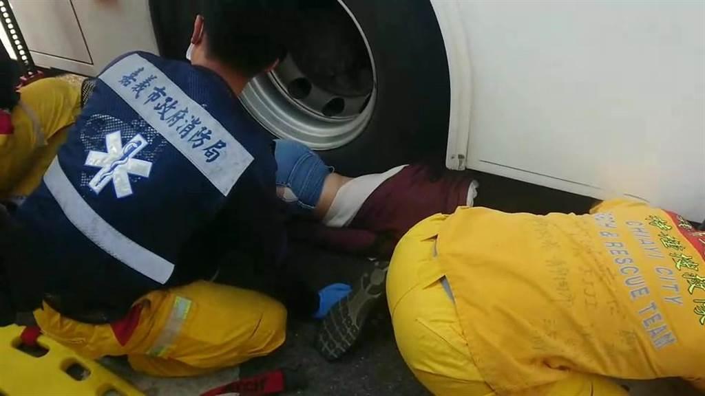 婦人被輾進嘉義客運BRT公車車底,嘉義市消防局人員搶救。(讀者提供/廖素慧嘉義市傳真)