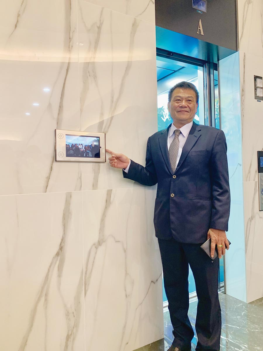 崇友電梯總經理游本立在崇友楊梅工廠展示中心親自示範人臉辨識智能電梯操作。圖/林宜蓁