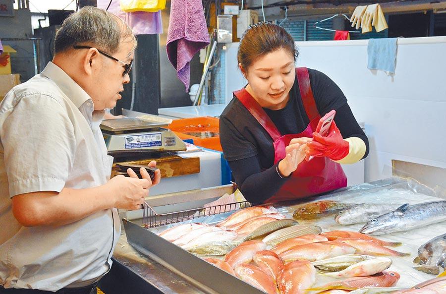 劉子菁(右)用手機與顧客確認商品,透過網購增加提袋率。(林和生攝)
