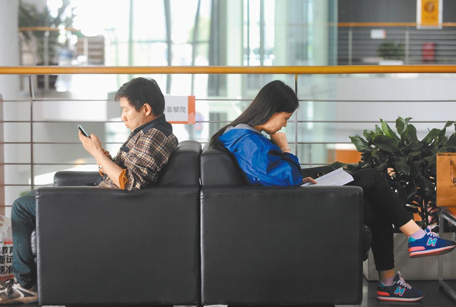 山西某一圖書館內,兩位市民分別對著電子螢幕和紙本圖書閱讀。(新華社資料照片)