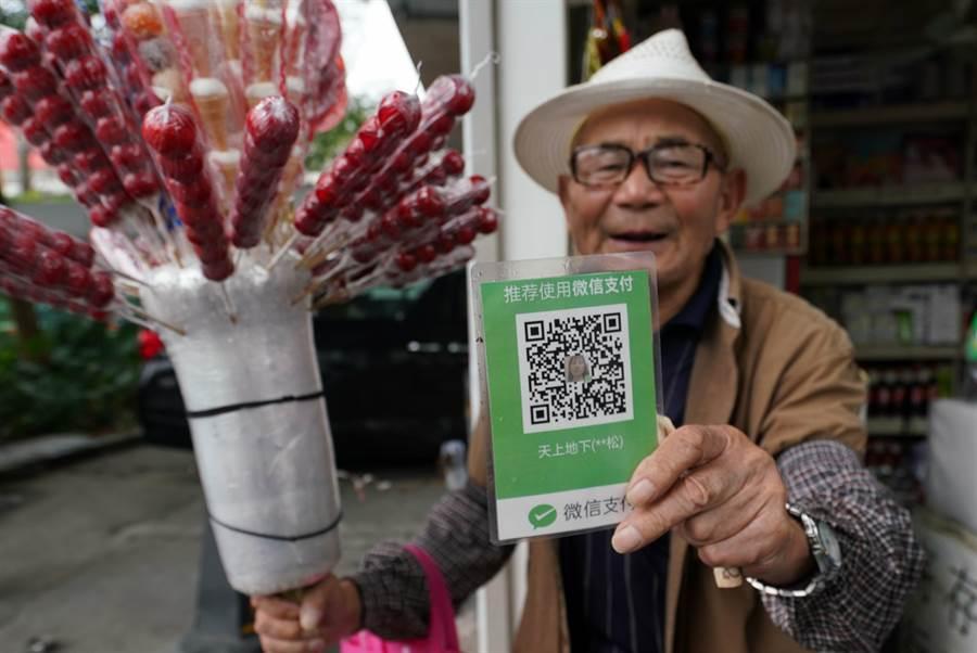 2018年,深圳街頭,一位賣糖葫蘆的商販向顧客出示行動支付QRCODE,方便顧客掃碼付錢。(中新社)
