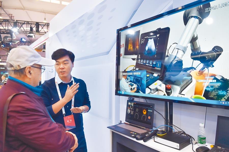 11月21日,在2019世界5G大會的展廳裡,工作人員介紹應用5G技術的遠程醫療。(新華社)