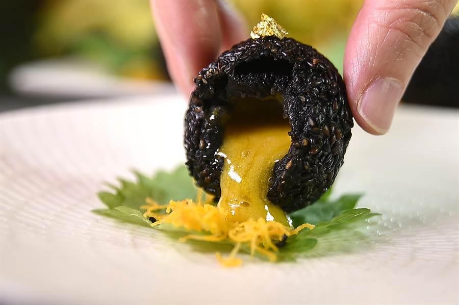 〈法國黑松露流沙芝麻球〉內餡是鹹蛋黃製成的奶黃流沙餡,一口咬下會「爆漿」。(圖/姚舜)